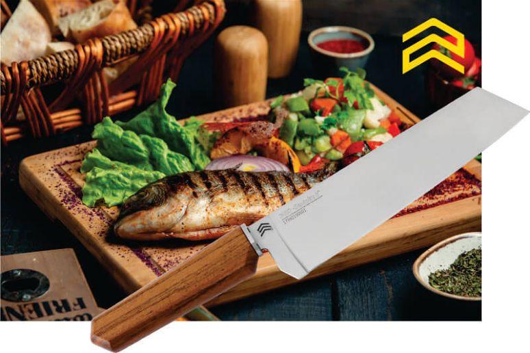 Peixe que foi feito na brasa em uma tábua de madeira com verduras ao lado