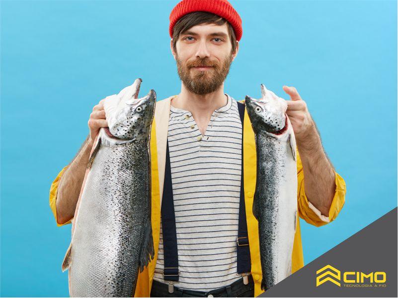 Pescador segurando dois peixes