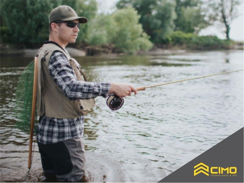 imagem de homem em um rio, vestido com cole e bone enquanto pesca