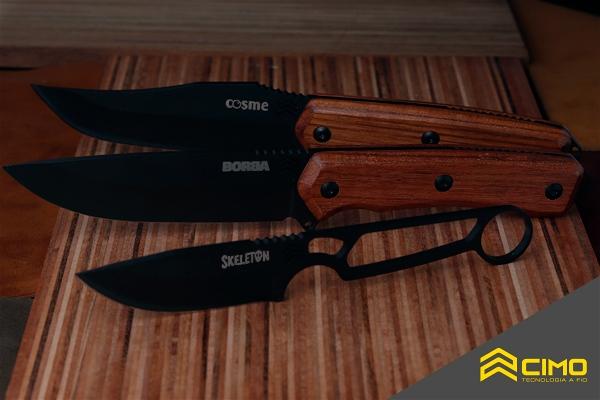 Imagem de 3 facas AX sobre uma tábua de madeira