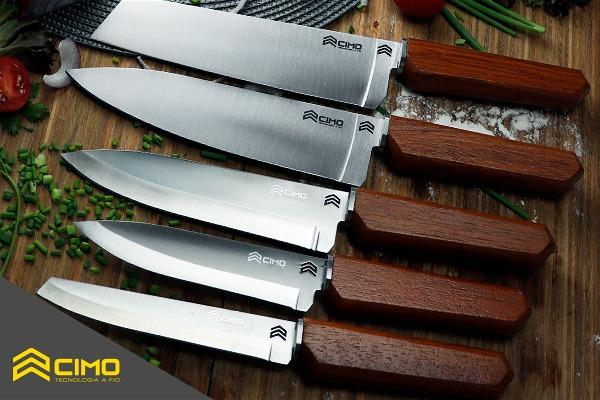 Imagem de facas do modelo Oiti sobre uma bancada de madeira, com tomates e especiarias ao redor