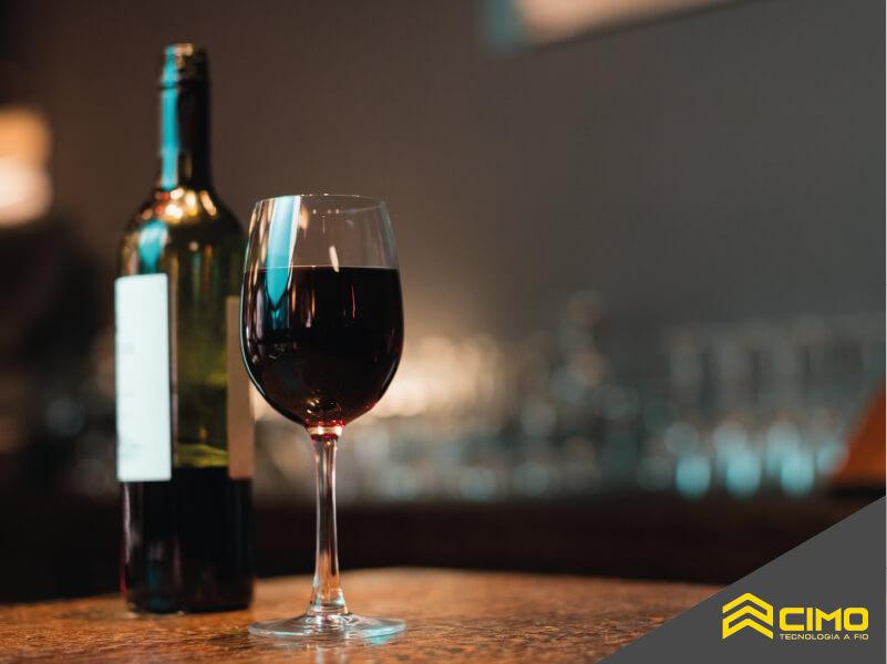 Imagem em destaque de taça de vinho ao lado de uma garrafa