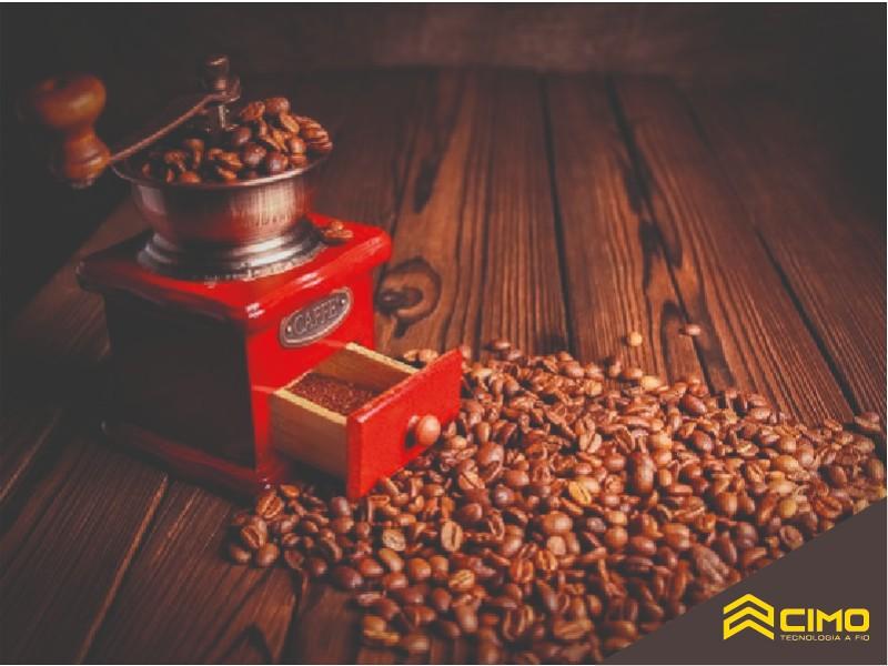 Moedor de café ao lado de pila de grãos