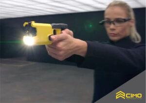 Mulher com óculos em um ambiente de testes segurando um taser