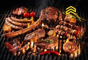 Diversos tipos de carne sendo grelhados em uma grelha de churrasco