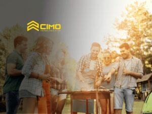pessoas sorrindo ao redor de uma churrasqueira