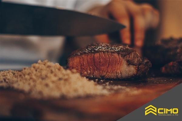 Imagem de um homem cortando uma peça de carne assada